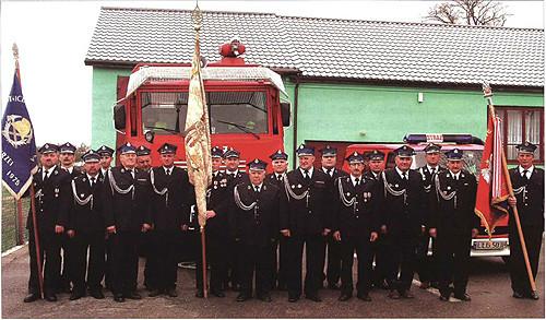 Zdjęcie jednostki miedzy wozami strażackimi przed remizą
