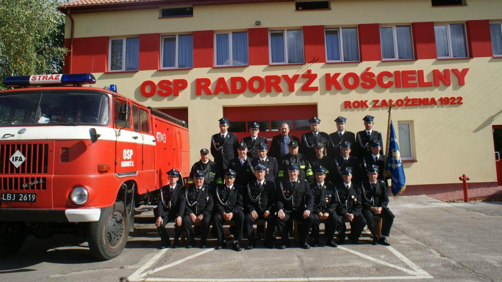 Zdjęcie jednostki strażeckiej u boku wozu strażackiego na tle remizy w Radoryżu Kościelnym
