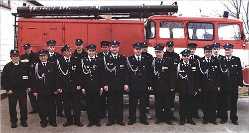 Zdjęcie jednostki strażackiej w Woli Okrzejskiej na tle wozu strażackiego