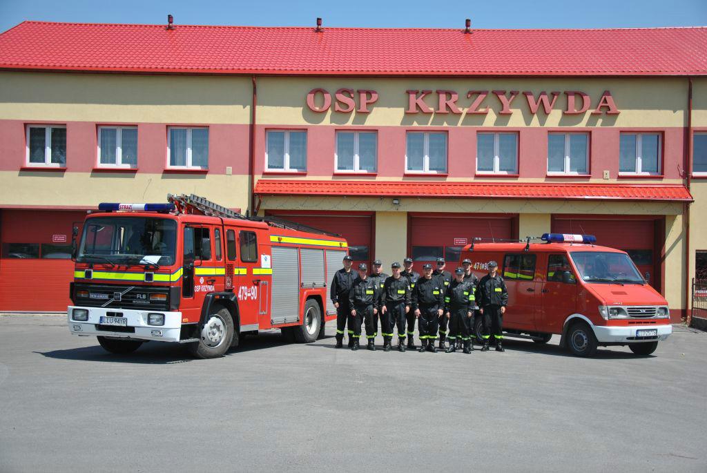 Zdjęcie jednostki w Krzywdzie między wozami strażackimi na tle remizy w Krzywdzie
